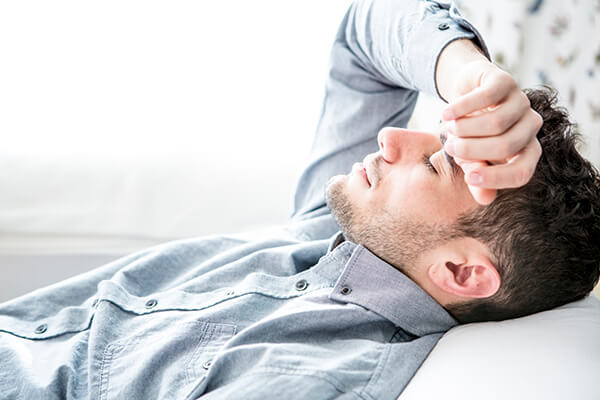 Man lying down and putting hand across forehead